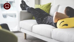 A man reclining on a white couch