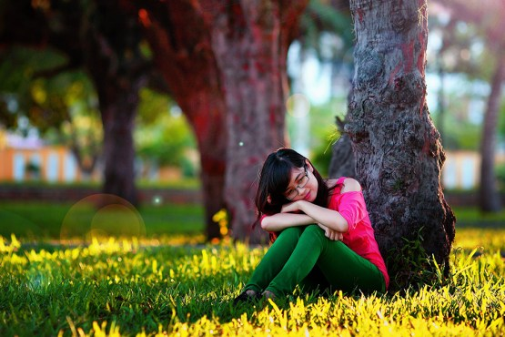 Mental Health - A girl sitting in the grass under a tree with her head resting on her knees