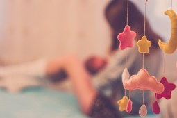 Signs and symptoms of postpartum depression - a woman is sitting down behind a baby mobile.