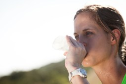 Woman standing outside drinking water