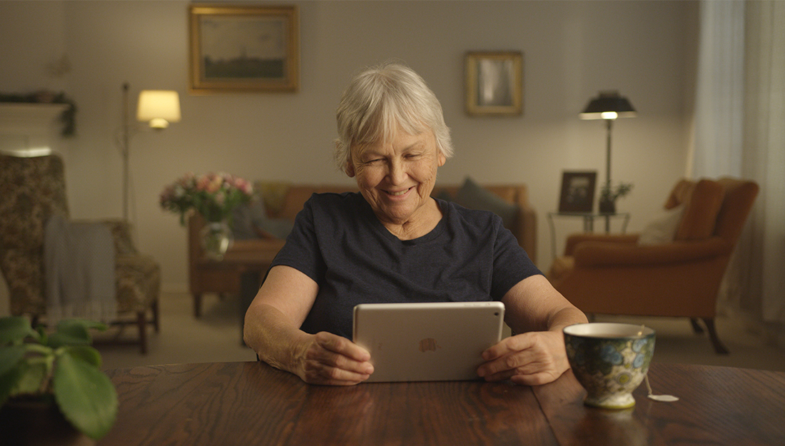 Woman smiling while looking at iPad