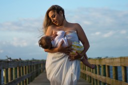 Breastfeeding_mastitis_blocked milk ducts_a woman holds her breastfeeding baby on a pier by the water