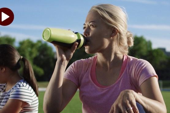 Dehydration_Hydration_a woman is sitting on a field drinking a water bottle