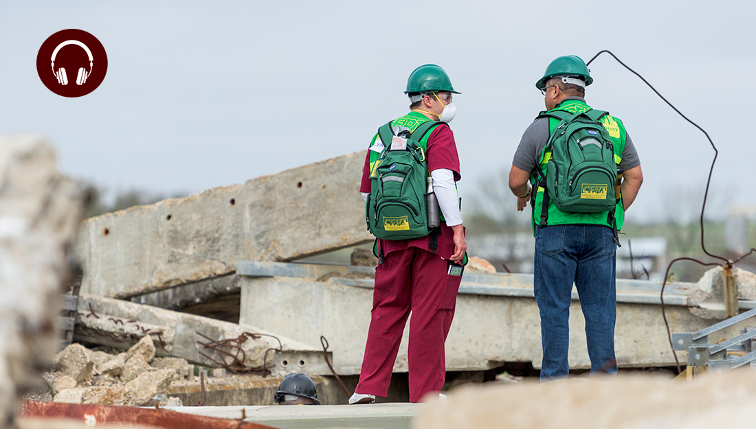 Disaster preparedness_Two students at Disaster Day are wearing head hats standing on fallen cement
