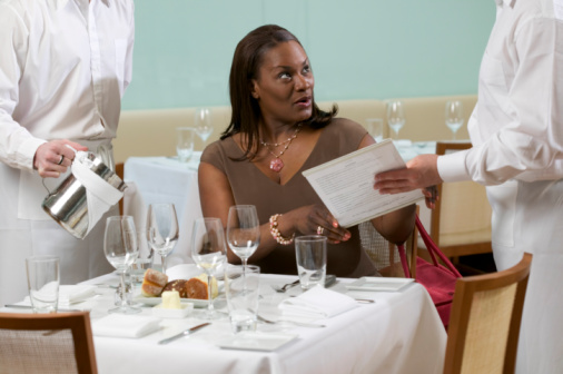 Woman in restaurant with waiters