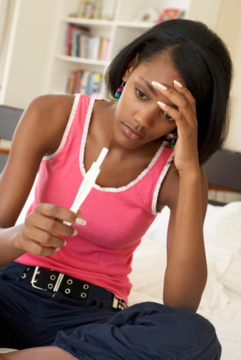 young black girl with pregnancy test
