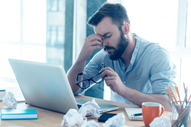 Frustrated guy looking at is computer messing with his nose