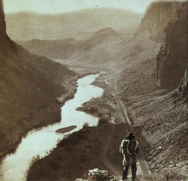A Native American overlooking the newly completed transcontinental railroad in 1868