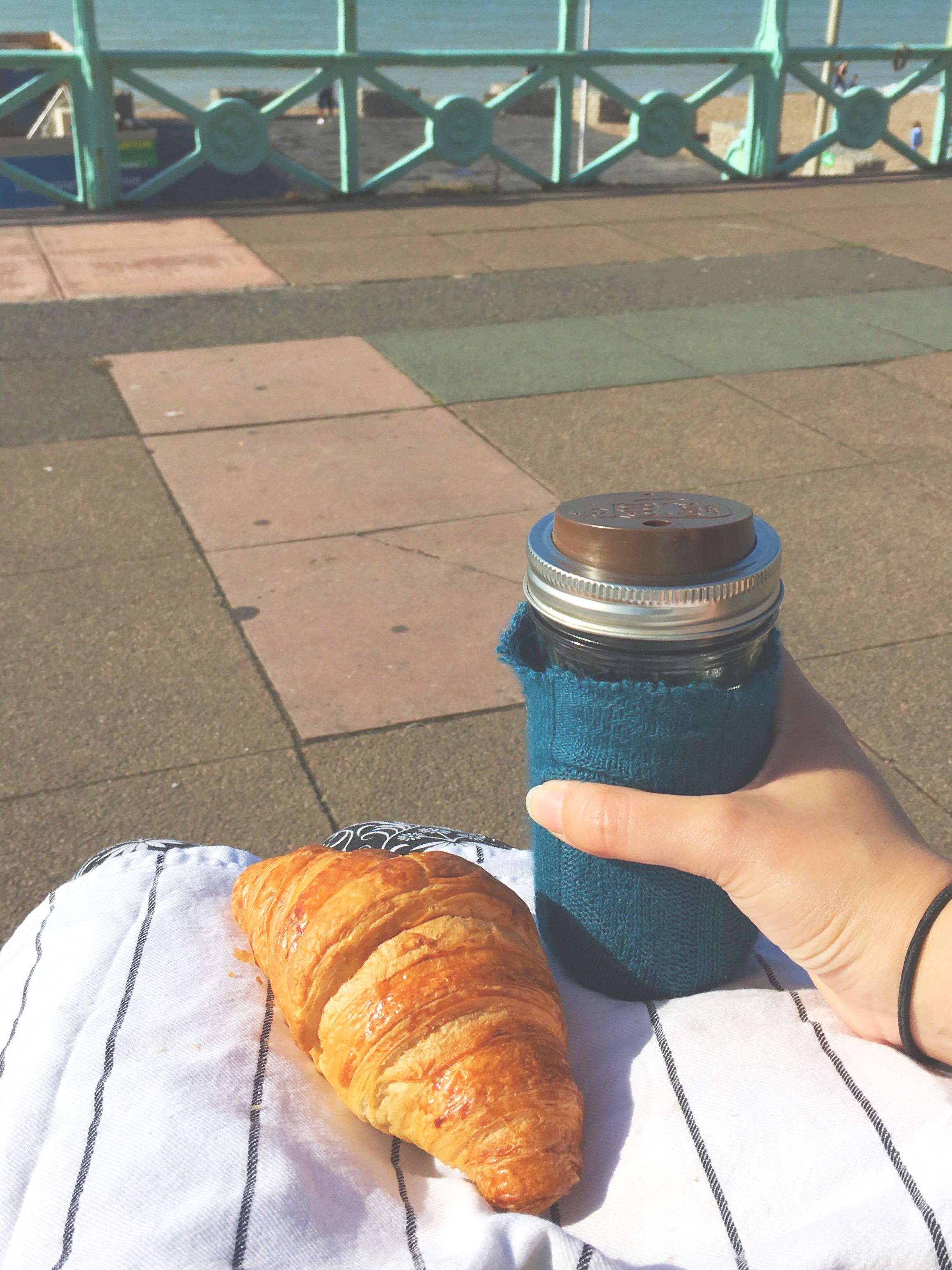 Meu copo-jarra preferido com café e um croissant que peguei com meu guardanapo de pano em uma cafeteria enquanto esperava meus colegas para pegar o trem de Brighton pra Londres.