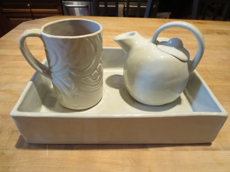 An embossed porcelain travel mug, a closed form teapot, and a rectangular casserole, all hand-built out of porcelain.