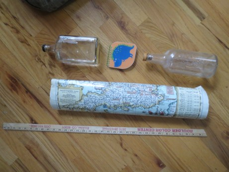 Glass bottles with stoppers, a map, a broken yard stick. A notepad.