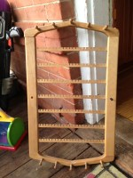 An earring rack that doesn't match the wood in my house. It needs a light sanding but it is otherwise in great condition. WHO WANTS IT?