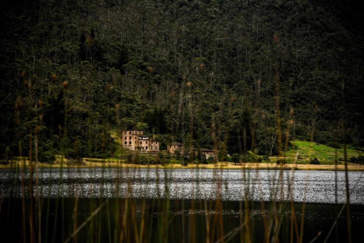 plantas de totora al borde de la laguna Llaviucu y en el horizonte los restos de una casa antigua.