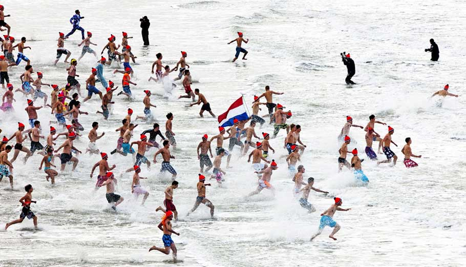 People run to take a bath in the North Sea during the Nieuwjaarsduik (New Year's dive) on New Year's Day in Scheveningen, Netherlands, on January 1, 2013.