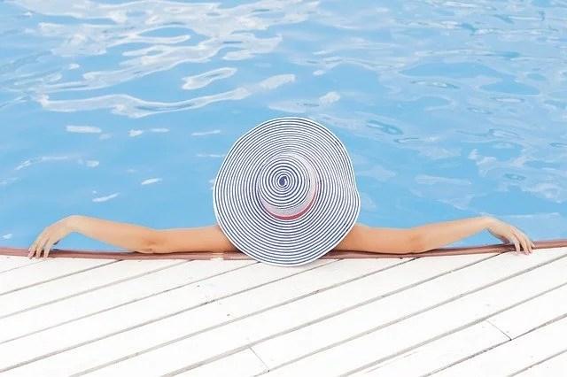 une fille au bord de la piscine avec un chapeau. Vacances déjà ressourcé