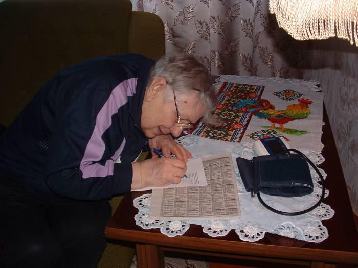 Надежда Марковна пишет заявление на отказ от установки пожароизвещателя. Фото Дарьи Максименко