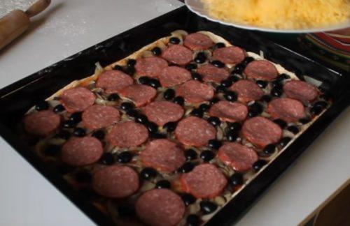 Pizza caseira com salame, cogumelos e azeitonas