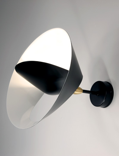 The Mouille Saturn lamp: a partial cut allows the outer edge to bend revealing a sculpted ring encircling a central cone reflector to both diffuse and project light into the room.