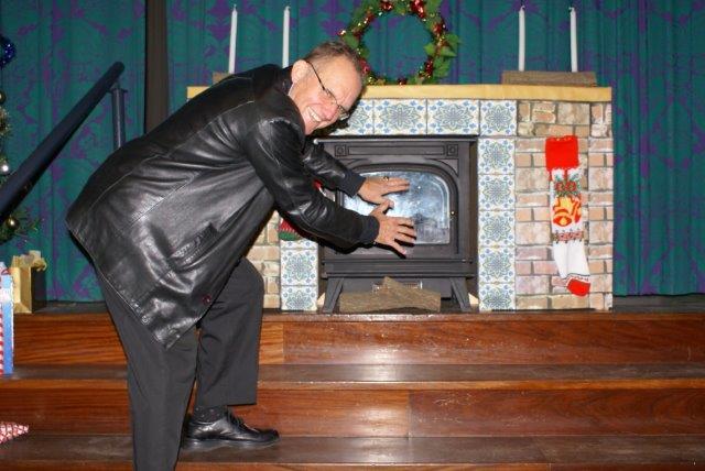 Pieter Ekermans maak sy hande warm by die kaggel.