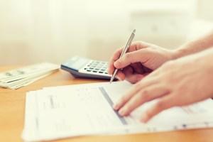 Someone organizing finances, calculator, money