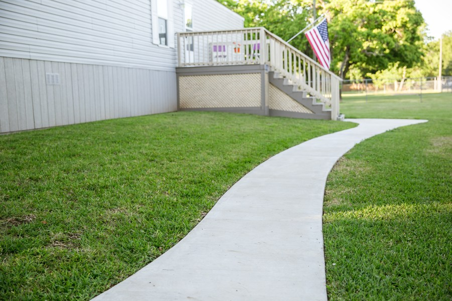 Exterior of manufactured home with from deck and a flag. Home has a paved sidewalk to the door.