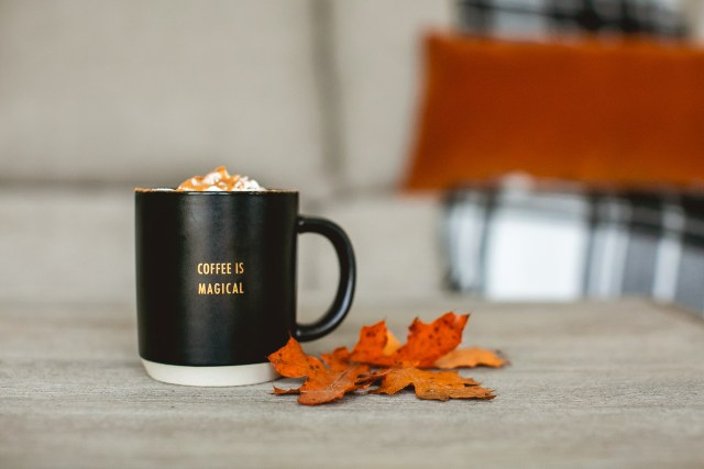 Cup of coffee with whip cream and caramel on a table next to fall leaves.