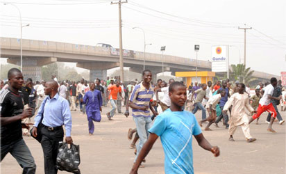 A RUN FOR SURVIVAL—People run for  safety at Kawo overhead bridge, Near I Div Hqtrs after a reported blast  in Kawo, Kaduna State yesterday. Photo: Olu Ajayi