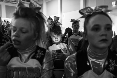 Kelsey Minnick, 19, uses a cell phone as members of the Dynamic Cheer Super Stars wait for their turn to perform at the Cheer and Dance Extreme Finale on Saturday April 9, 2016 in Virginia Beach, VA.