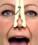 Person singing with a peg on her nose - representing nasal singing