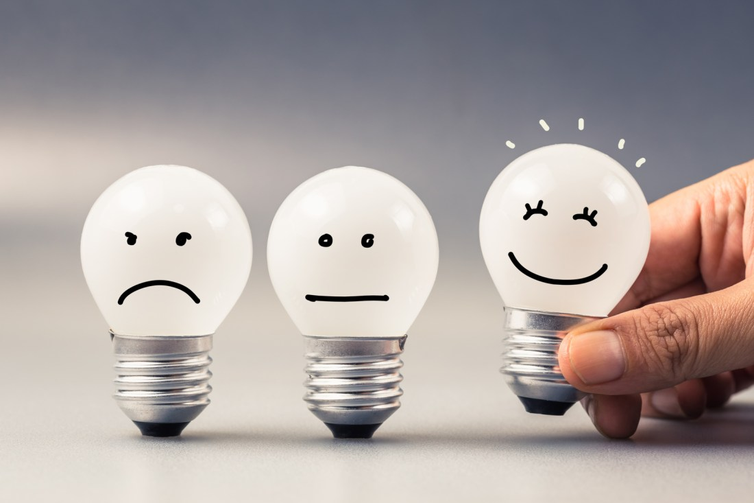 Hand choosing a smiling light bulb from a set of three satisfaction evaluation light bulbs