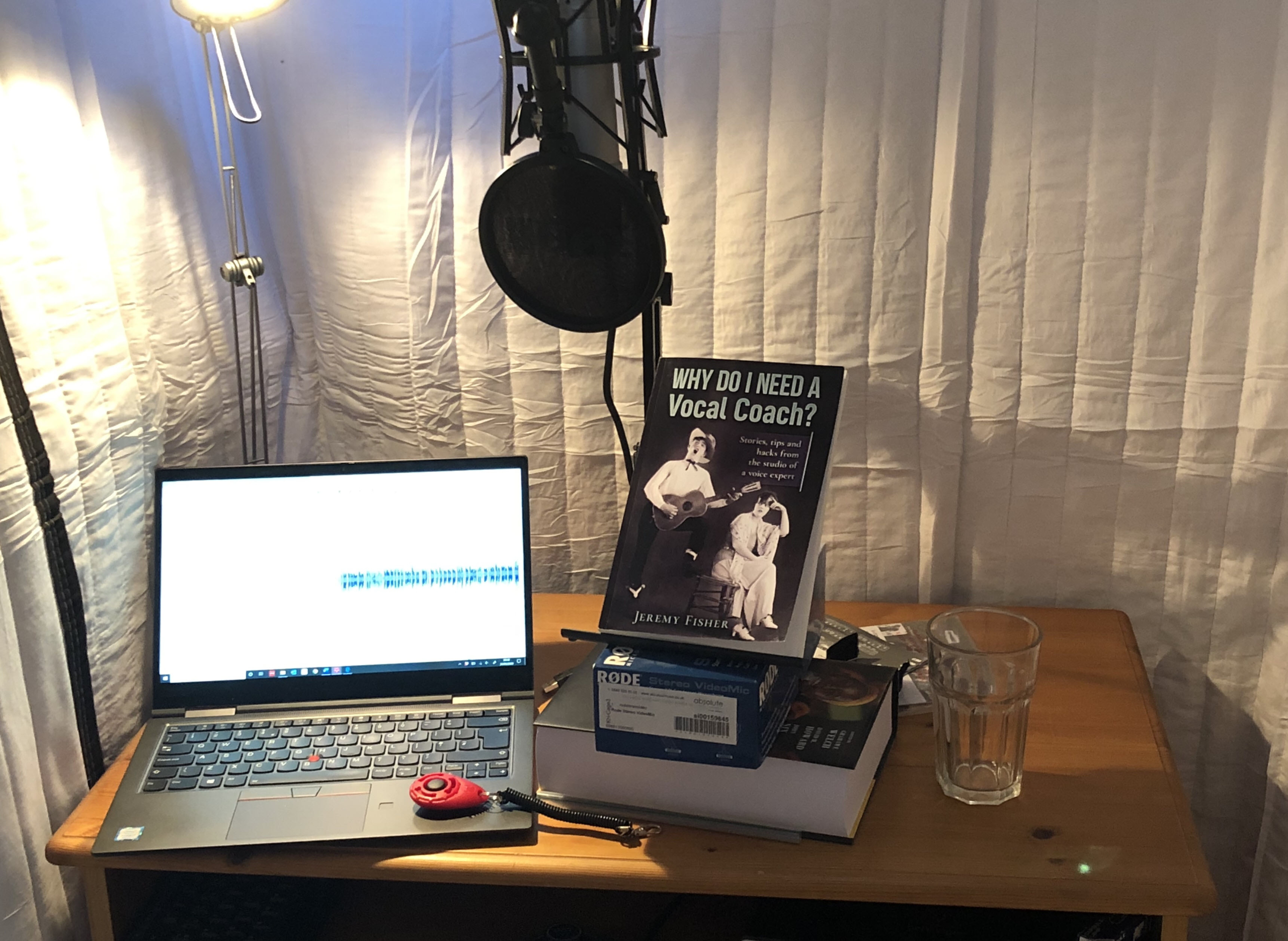 Jeremy Fisher's voiceover booth with laptop, suspended microphone, book and recording equipment