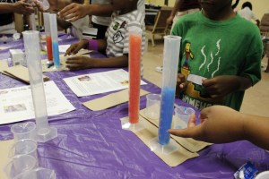 Students observe a chemical reaction with 2 different outcomes, then discuss their observations about whether the size of one reactant, a tablet they broke into small size pieces in the red cylinder and into large size pieces in the blue cylander, made the red liquid rise higher and faster than the blue liquid.
