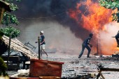 Rohingya men are seen among houses set on fire during fighting