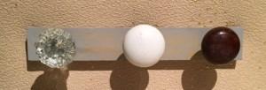 grey rectangular pine holds three vintage doorknobs; one crystal, one white and one dark brown.