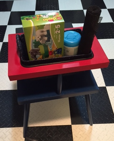 Table from behind shows red top with cutout where basket full of toys fits snugly