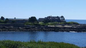Massive home with several large homes beside it spread along a spit of land jutting into the ocean, separated from the mainland