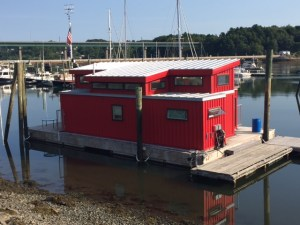 Red home/boat is built entirely from shipping containers
