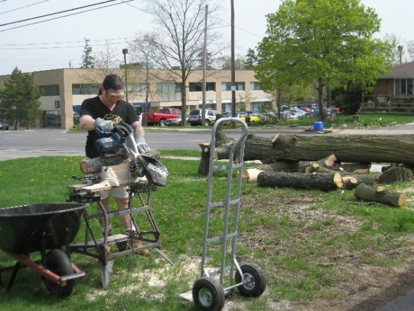 Derek cutting up wood with the rest of a downed tree in the background