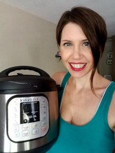 Woman holds her Instant Pot - a programmable, stainless-steel pot with a black lid