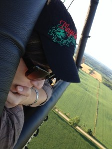 close-up of me looking over the edge of the balloon with farmer's fields far off in the background