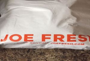 Unopened white delivery bag sits on the kitchen counter with the words Joe Fresh in bold orange