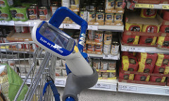 scan as you shop gizmo attached to the handle of a shopping cart