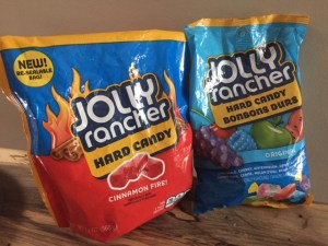 two bags of Jolly Ranchers candy. One is Cinnamon Fire, the other is assorted.