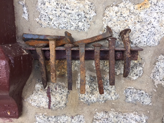 a collection of rusted railway spikes hangs like a sculpture near the entrance to the station