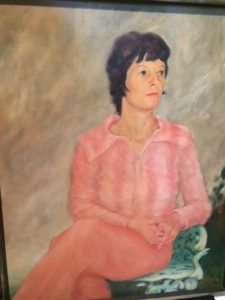 painting of my Mom. She has short, dark hair and is wearing a pink pantsuit, sitting on a white chair with her legs crossed and arms folded, looking off to the left