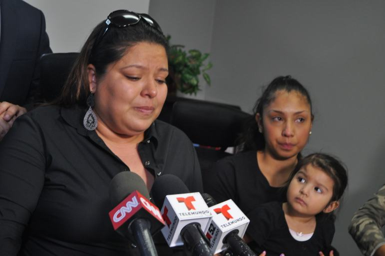 Mayte Canepa (left) speaks to media Tuesday afternoon about the police shooting death of her brother, Ernesto Javier Canepa Diaz. Seated next to her is Ernesto Canepa's wife, Jazmin Canepa, and their two-year-old daughter Mia Canepa.