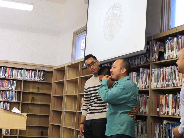 Santa Ana Boys and Men of Color Project Director Abraham Medina and Youth Engagement Coordinator Ignacio Rios Jr. praise Adrian's progress during a Joven Nobel graduation ceremony.