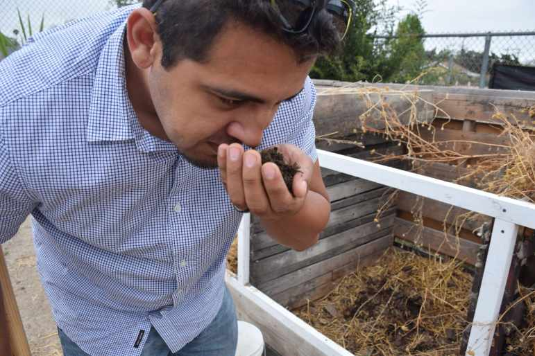 Moises Plascencia checks compost made at the farm.