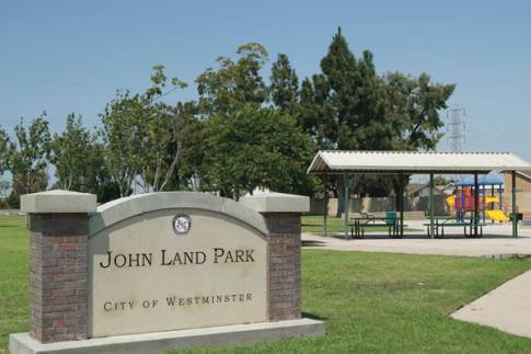 Westminster John Land Park – Westminster's John Land Park includes play equipment, a shade structure with picnic benches and well-kept grassy areas.