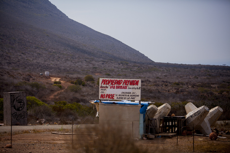 A sign on land claimed by a Mexican rancher and Sempra Energy next to the company's natural gas plant outside Ensenada, Mexico. // Photo by Sam Hodgson
